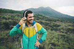 Happy smiling traveler listening music in the field near mountain. Intentional pale color style Stock Image