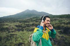 Happy smiling traveler listening music in the field near volcano. Intentional pale color style Stock Photography