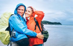 Happy smiling travelers couple in rainy day on the ocean beach Stock Image