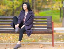 Happy smiling trendy young woman on a bench. stock image
