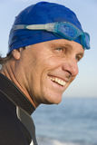 Happy smiling triathlete. A color portrait photo of a happy smiling triathlete wearing swimming goggles and a swimming cap Royalty Free Stock Photo