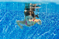 Happy smiling underwater child in swimming pool Royalty Free Stock Images