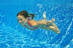 Happy smiling underwater child in swimming pool Stock Photography