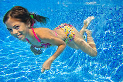 Happy smiling underwater child in swimming pool Royalty Free Stock Photo