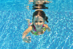 Happy smiling underwater child in swimming pool Stock Photo