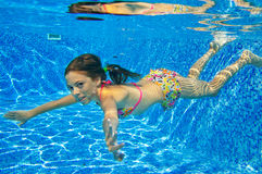 Happy smiling underwater child in swimming pool Royalty Free Stock Image