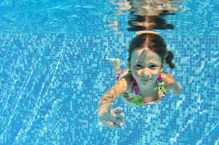 Happy smiling underwater child in swimming pool Royalty Free Stock Photos