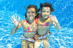 Happy smiling underwater children in swimming pool Royalty Free Stock Photo
