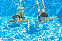 Happy smiling underwater children in swimming pool. Beautiful healthy girls swim and having fun. Kids sport on family summer vacation. Active holiday Stock Photo