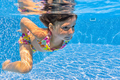 Happy smiling underwater kid in swimming pool Stock Images
