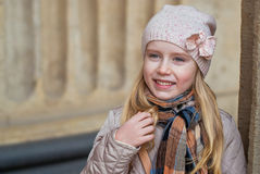 Happy smiling urban girls. Happy smiling girl on a city street, dressed in scarf and hat Royalty Free Stock Photos