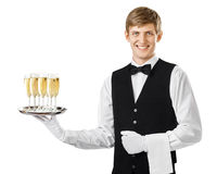 Happy smiling waiter serving champagne on a tray Stock Image