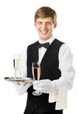 Happy smiling waiter serving champagne on a tray Stock Photography