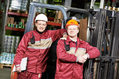 Warehouse workers in front of forklift Stock Photo