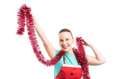 Happy smiling wife or maid dancing with Christmas tinsel garland. Wearing red apron isolated on white background Royalty Free Stock Images