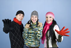 Happy smiling winter friends. Happy smiling three friends showing happiness and excitement and standing with hands gloves in front of image over blue background Royalty Free Stock Image