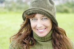 Happy smiling woman. A color portrait of a happy smiling mature woman in her forties wearing a green hat and jumper. She also has brown hair and freckles Royalty Free Stock Image