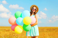 Happy smiling woman with an air colorful balloons enjoying a summer day on a field and a blue sky background Royalty Free Stock Photography