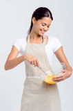 Happy smiling woman beating eggs Stock Images