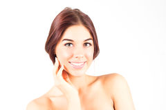 Happy and smiling woman with a beautiful and clean skin touching cheek. SPA and beauty treatment. Stock Photo