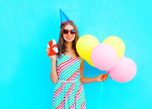 Happy smiling woman in a birthday cap with a gift box on hands, an air colorful balloons over blue background Stock Images