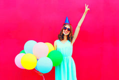 Happy smiling woman in a birthday cap having fun over an air colorful balloons pink Stock Image