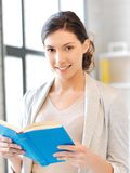Happy and smiling woman with book Royalty Free Stock Image