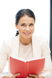 Happy and smiling woman with book Royalty Free Stock Photography