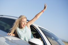 Happy smiling woman in car very happy out of window with funny e. Xpression stock photo
