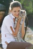 Happy smiling woman with cat. Young happy smiling woman with cat on natural background Royalty Free Stock Photos