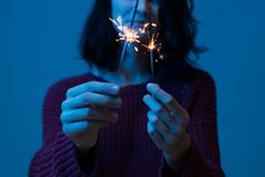 Happy smiling woman celebrating with fireworks. Girl holding a bengal light new year party. stock image