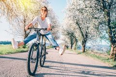 Happy smiling woman cheerfully spreads legs on bicycle on the country road under blossom trees. Spring is comming concept image