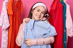 Happy smiling woman chooses blouse. Satisfied lady likes purchase. Brunette embraces hanger with blue shirt. Pretty girl in stock images