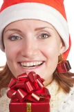 Happy smiling woman in christmas hat with gift Royalty Free Stock Photography