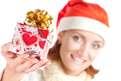 Happy smiling woman in christmas hat with gift Stock Photos