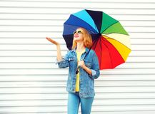 Happy smiling woman with colorful umbrella, checks rain on white. Background stock photography