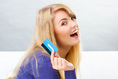 Happy smiling woman with credit card, concept of cashless paying for shopping. Happy smiling woman holding credit card in hand, concept of cashless paying for Royalty Free Stock Photos