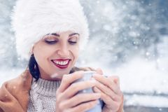 Happy smiling Woman with cup of hot tea in snow forest royalty free stock photos