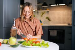 Free Happy Smiling Woman Cutting Fresh Organic Tomato With A Knife For Vegetable Salad. Stock Image - 189563961