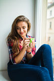 Happy cute smiling woman drinking tea while sitting on the windowsill Stock Photos