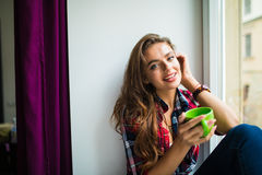 Happy cute smiling woman drinking tea while sitting on the windowsill Stock Image