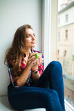 Happy cute smiling woman drinking tea while sitting on the windowsill Royalty Free Stock Images