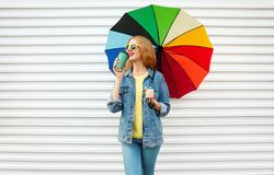 Happy smiling woman drinks coffee, holds colorful umbrella on white. Wall background stock photo