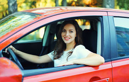 Happy smiling woman driver behind wheel red car Stock Photos