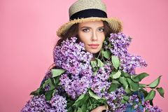 Happy smiling woman enjoying smell of bouquet lilac flowers over colorful blue background royalty free stock photo