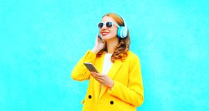happy smiling woman enjoys listens to music in headphones holds smartphone Royalty Free Stock Images