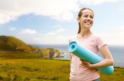 Happy smiling woman with exercise mat over big sur royalty free stock images