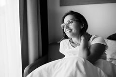 Happy smiling woman in eyeglasses meets new day in bedroom Stock Photo