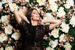 Happy smiling woman on flower wallpaper background. In studio photo. Beauty concept. Floral decoration Stock Image