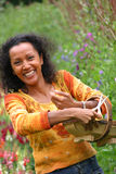 Happy smiling woman in garden. Beautiful smiling black woman in garden cutting flowers Stock Photography